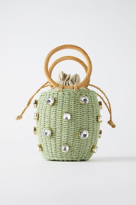 Green basket format bag. Braided body with jewellery detail. Circular handgrips.