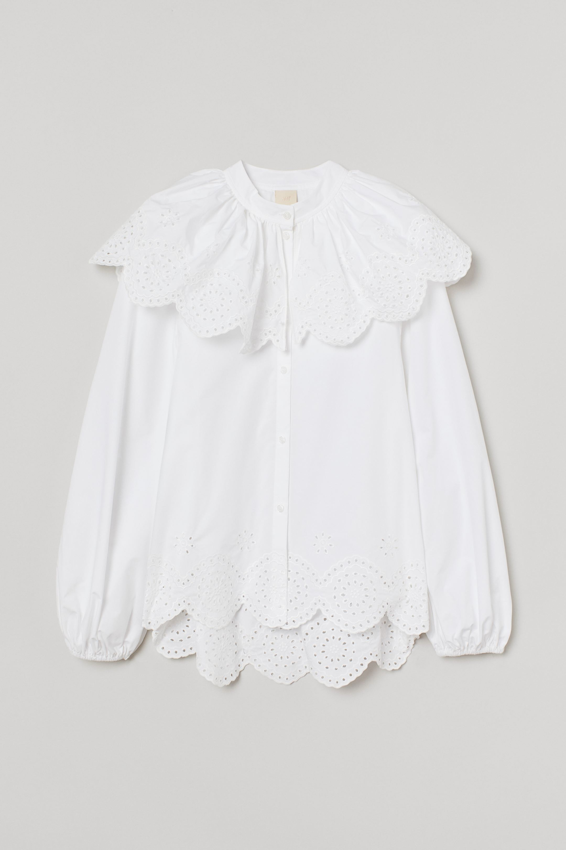 Wide cotton blouse with English embroidery, short turtleneck with semi-loose layer covering the shoulders. Buttons in front, long balloon sleeves with fine elastic lining on the cuffs and scalloped hem.