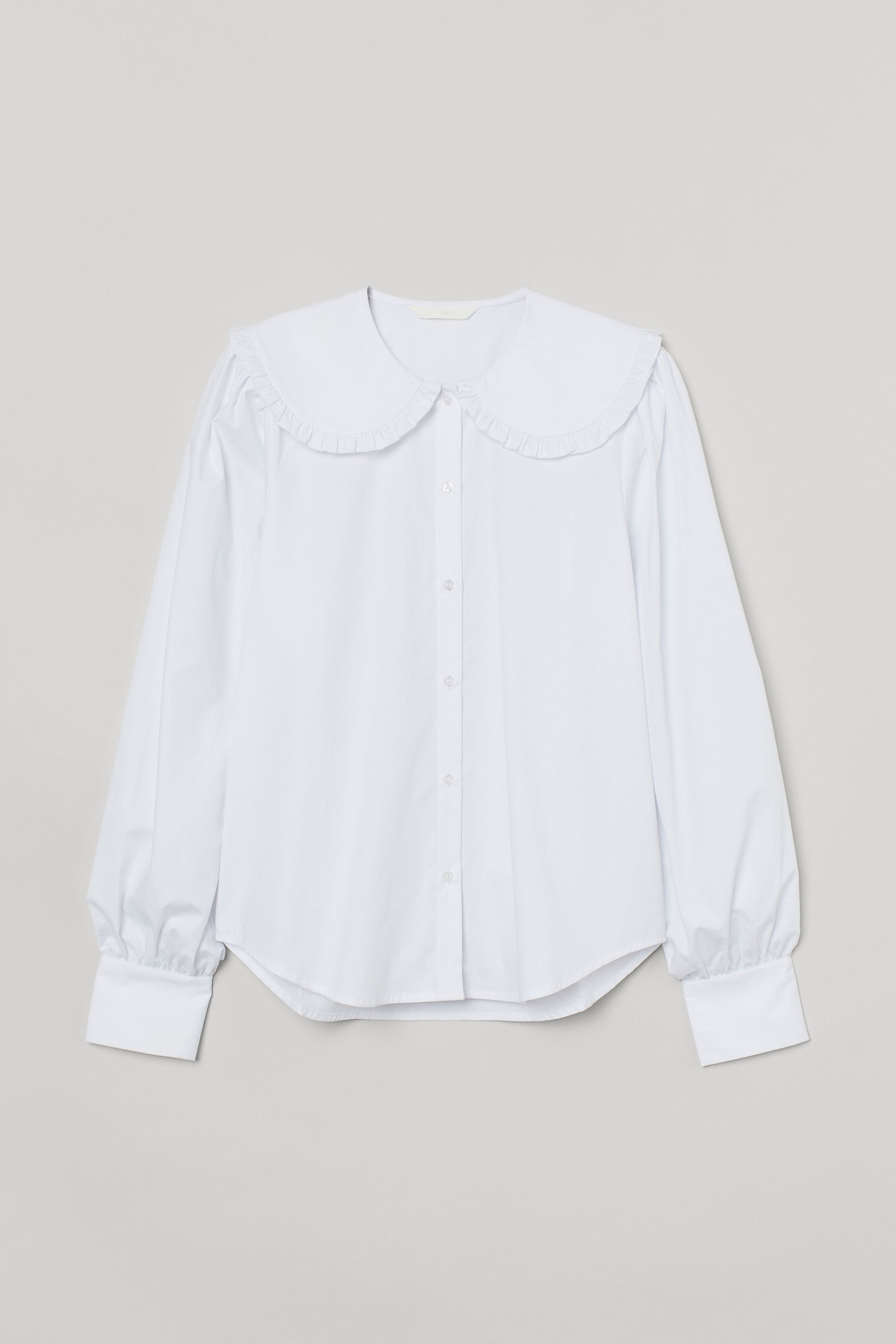 Vaporous cotton blouse with wide double collar with ruffle and button closure. Straight cut model with long sleeves, wide buttoned cuffs and rounded bottom with slightly longer back.