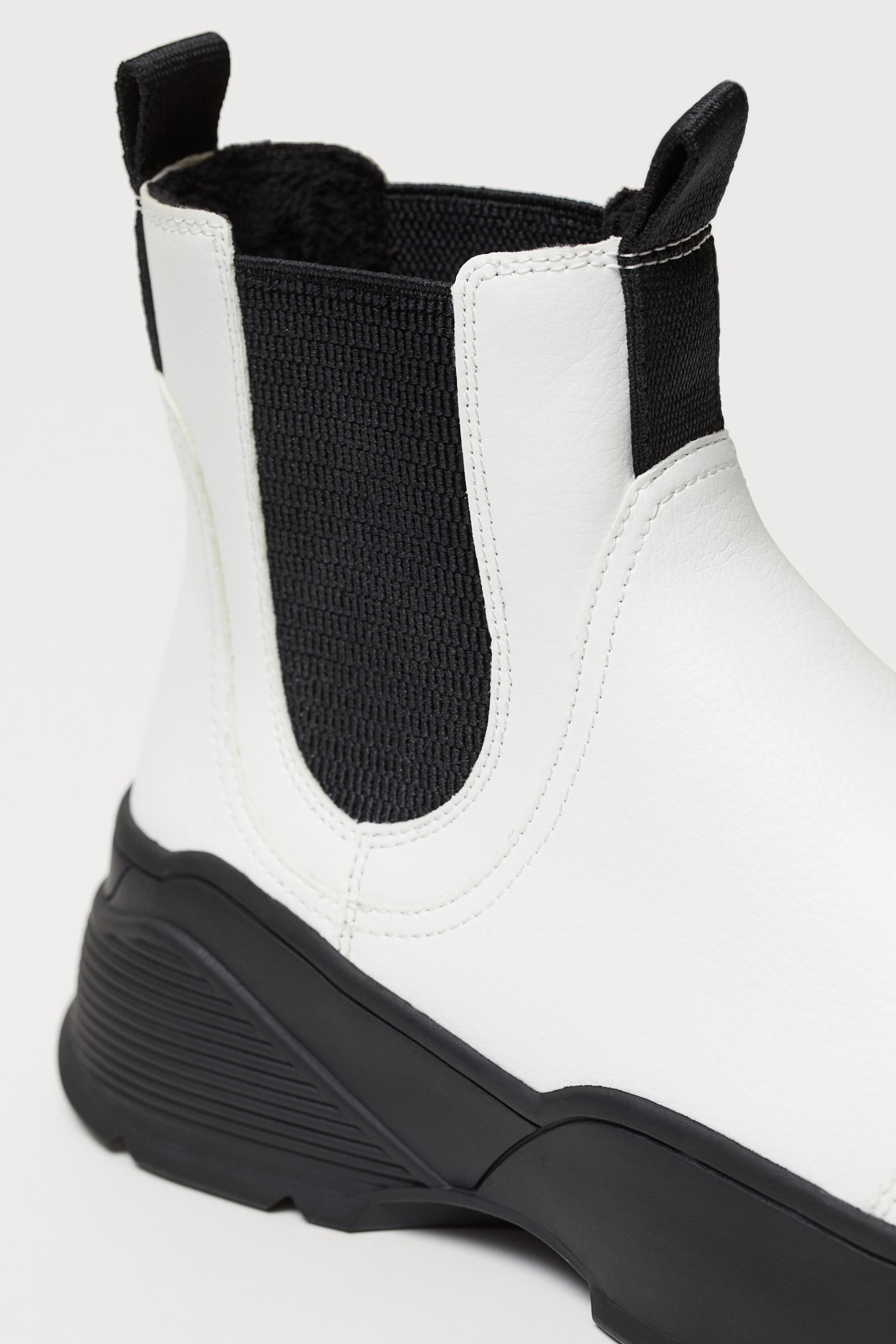 Chelsea boots in synthetic leather with side elastics and front and back belt loops. Lined and stuffed insole. Thick sports sole.