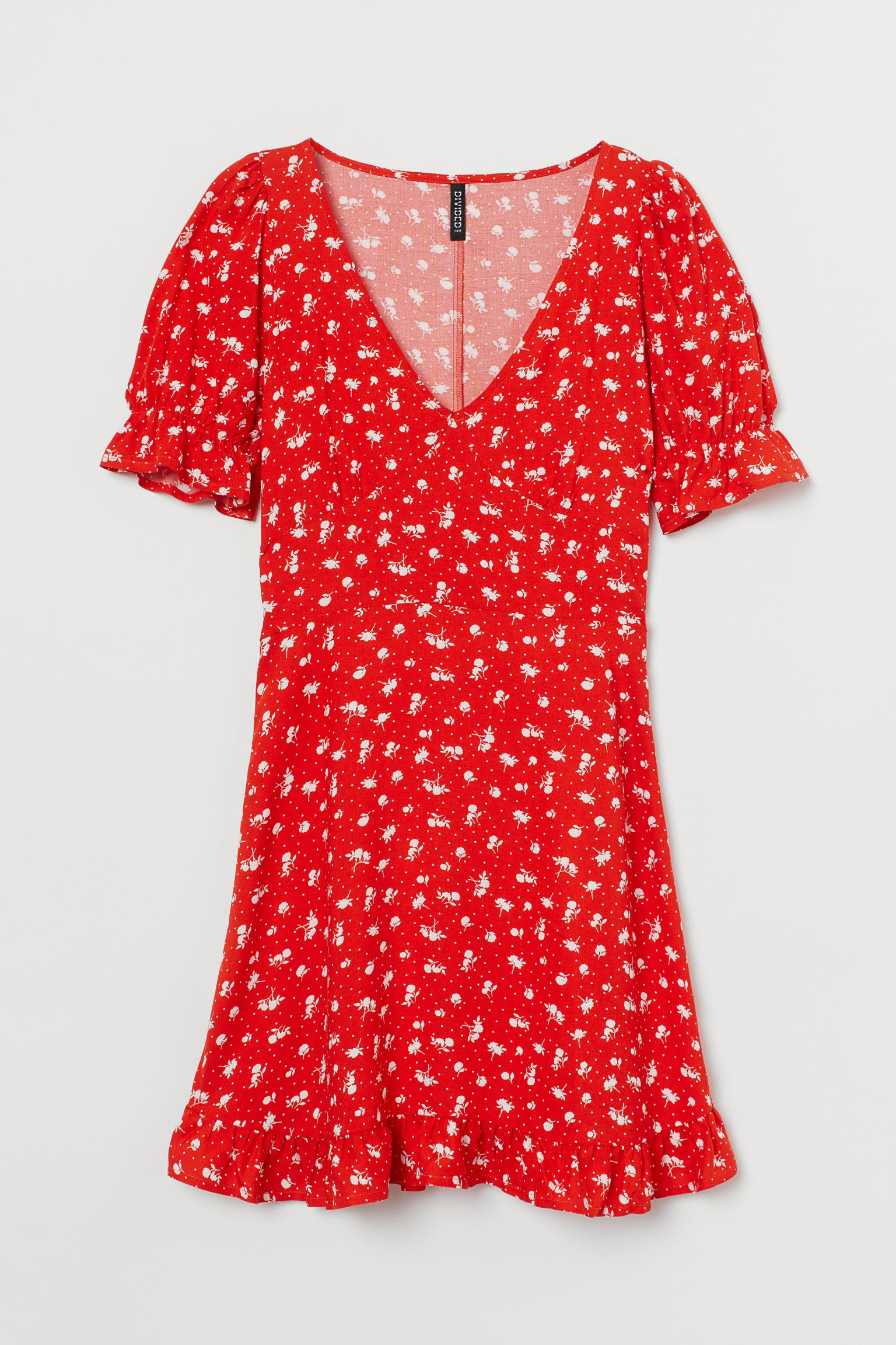Short printed dress in viscose with V-neckline and seam under the bust. Model with short puffed sleeves with elastic and ruffle trim, sewn straps at the back of the waist and hidden zipper on one side.