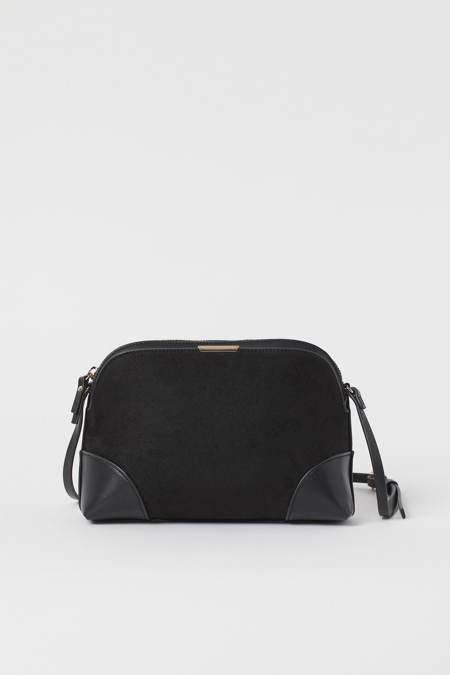Small shoulder bag in synthetic leather and suede with zipper at the top and adjustable thin strap. An outer compartment with magnetic closure and an inner compartment with zipper.