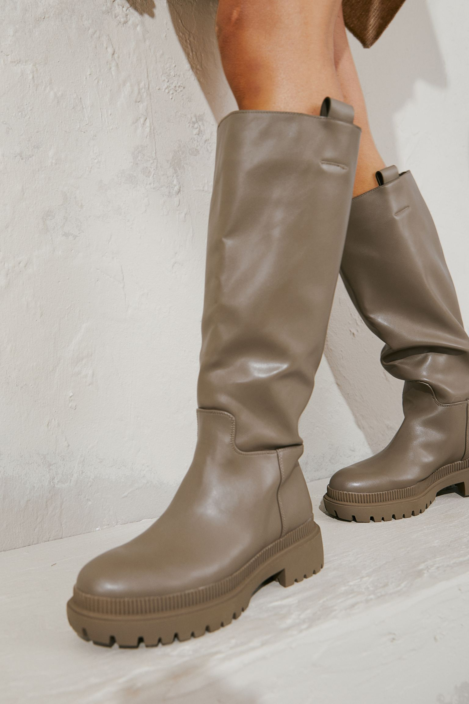Knee boots in faux leather with side straps. Satin lining and synthetic leather insole. Thick sole with design. Heel 5,5 cm.